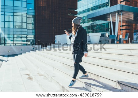 Young beautiful caucasian woman walking downstairs outdoor in the city back light, looking the screen of a smart phone hand hold - technology, social network, communication concept - stock photo