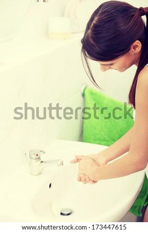 Young beautiful caucasian woman washing hands in bathroom. - stock photo