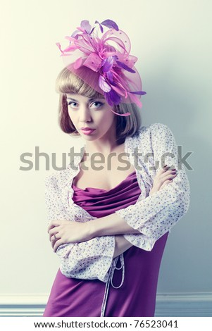 Young beautiful caucasian woman wearing a fancy hat with feathers - stock photo