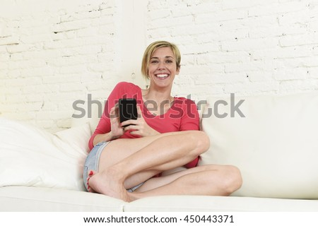 young beautiful Caucasian woman with shorts and modern hair style happy on couch using internet texting on mobile phone relaxed and cheerful at home living room in communication concept - stock photo