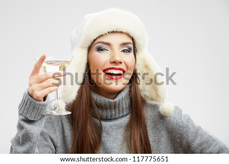 Young beautiful celebrate woman drink wine. Smiling female model holiday portrait with winter hat. - stock photo