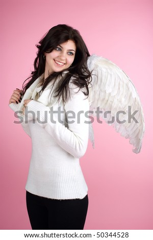 Young beautiful cheerful girl in angel suit over pink background. - stock photo