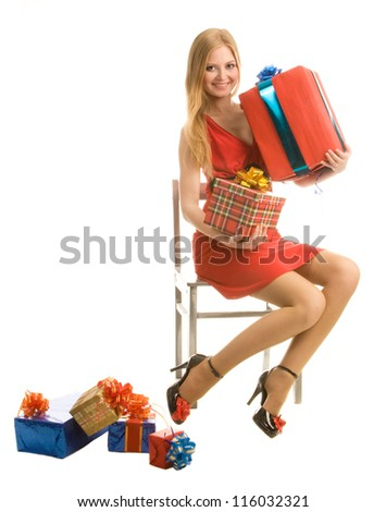 Young beautiful cheerful girl sits, holds gift boxes, isolated on  white background