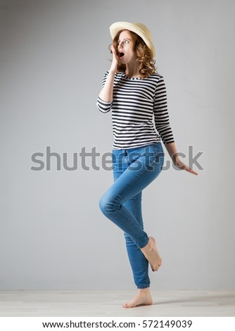 Young beautiful cheerful woman on a grey background