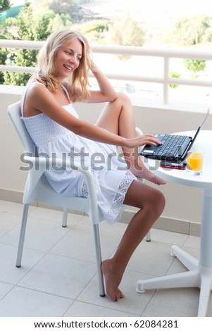 young beautiful cheerful woman with a laptop (high key) - stock photo