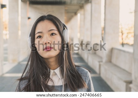 Young beautiful Chinese girl with headphones listening to music in the city streets - stock photo