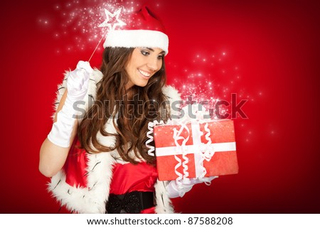 young beautiful Christmas fairy with magic wand and Christmas present - stock photo