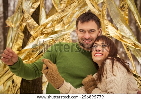 Young beautiful couple and burning sparklers. Loving couple wearing warm sweater in Christmas decorated - stock photo