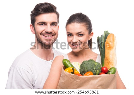 Young, beautiful couple are holding a bag full of vegetables, on white background. - stock photo