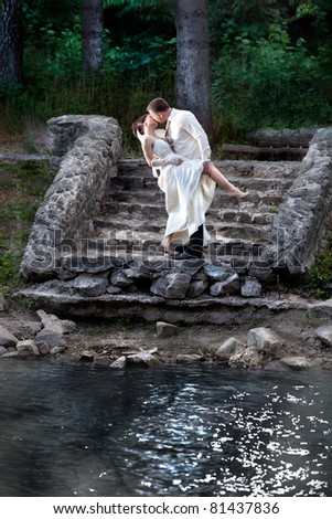Young beautiful couple dressed in white kissing near riverside - stock photo