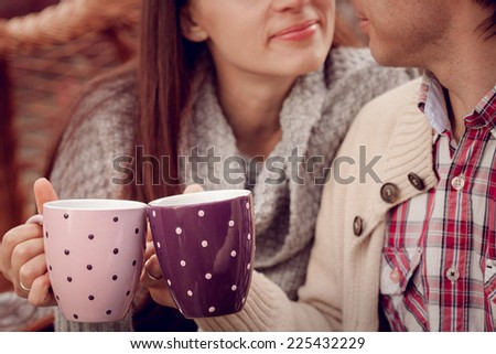 Young beautiful couple drinking tea outdoors - stock photo