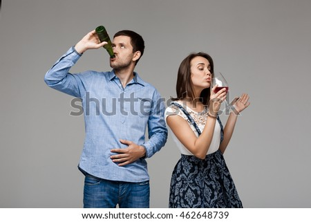 Young beautiful couple drinking wine and beer over grey background.