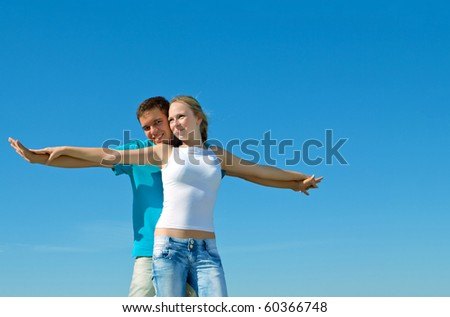 young beautiful couple embracing against blue sky - stock photo