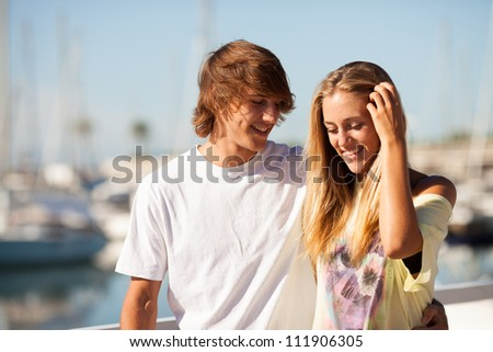 Young beautiful couple enjoying a walk by the harbour