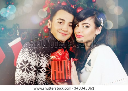 young beautiful couple exchanging gifts at Christmas - stock photo