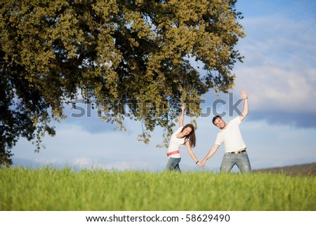 Young beautiful couple hand by hand doing some sport movements under a tree. - stock photo