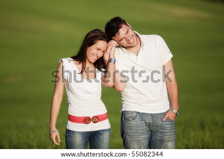 Young beautiful couple hand by hand isolated on natural green background. - stock photo