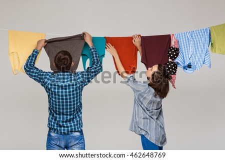 Young beautiful couple hanging wash clothes over grey background.