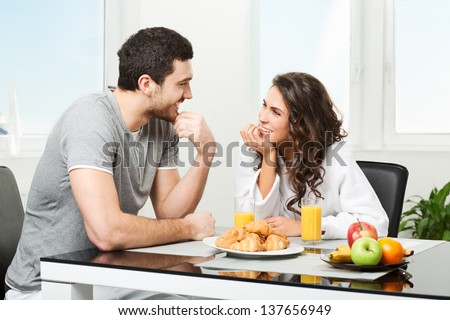 young beautiful couple having breakfast table - stock photo