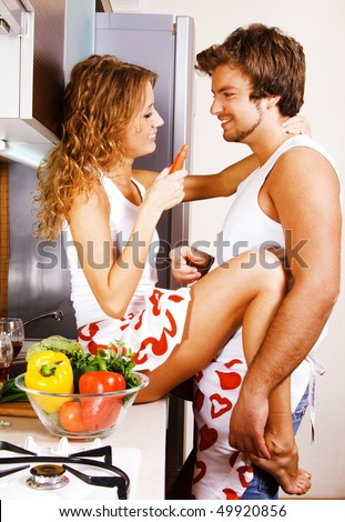 Young beautiful couple having fun in the kitchen - stock photo