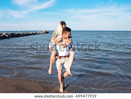 Young beautiful couple having fun on the beach