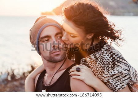 Young beautiful couple hugs at sunshine near the seaside. Warm sunny colors. Fashion closeup outdoor portrait. - stock photo