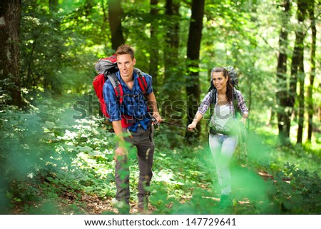 Young beautiful couple in a forest, hiking at summertime.  - stock photo
