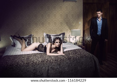 Young beautiful couple in bedroom - stock photo