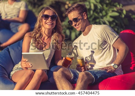 Young beautiful couple in casual clothes and sun glasses is using a digital tablet, holding bottles of beverage and smiling, sitting on bean bag chairs outdoors - stock photo