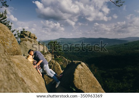 Young beautiful couple in jeans and shirts for a walk in the mountains. Guy kisses and hugs girl, expressing love and passion