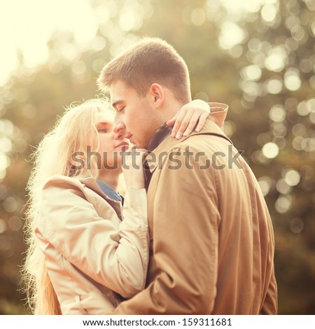 Young beautiful couple in love in park - stock photo