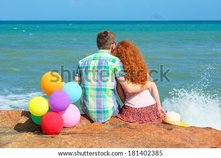Young beautiful couple in love sitting  coast while honeymoon. Young woman kisses with her handsome man - stock photo