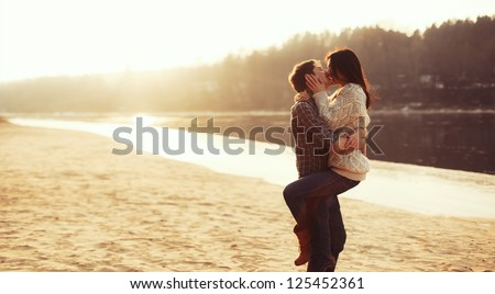 Young beautiful couple in love staying and kissing on the beach on sunset. Soft sunny colors.