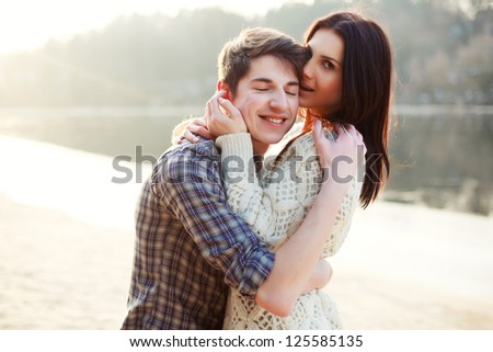 Young beautiful couple in love staying on the beach in evening sunshine. Happy smiling boy and girl - stock photo