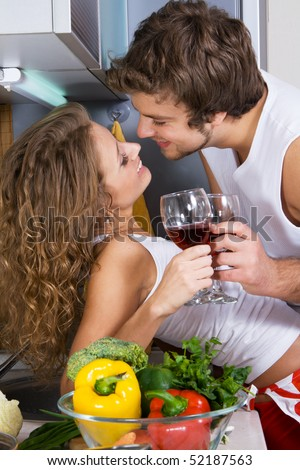 Young beautiful couple in their kitchen - stock photo