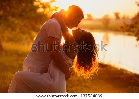 Young beautiful couple in white dancing on the background of sunset - stock photo