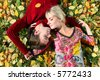 young beautiful couple is laying on the autumn grass - stock photo
