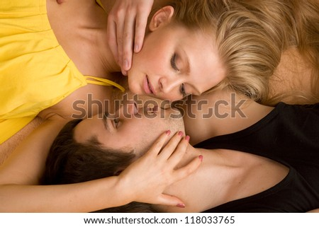 Young beautiful couple is lying on the bad face to face. Top view, close up