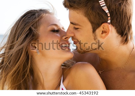Young beautiful couple kissing at the sea shore - stock photo