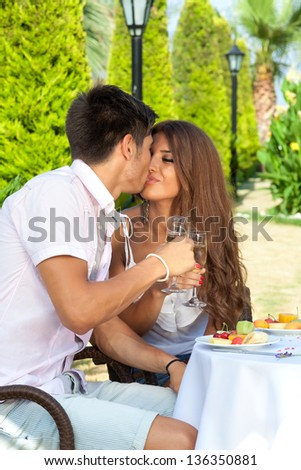 Young beautiful couple kissing while having a fancy lunch outside in a warm sunny day