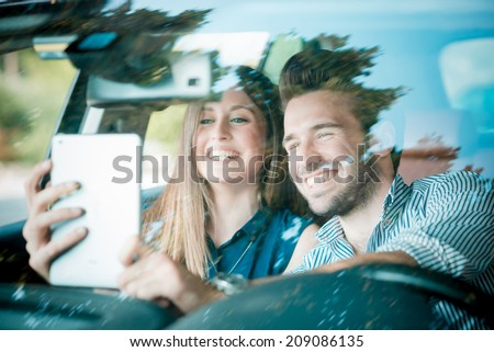 young beautiful couple lovers using tablet in the car travel - stock photo
