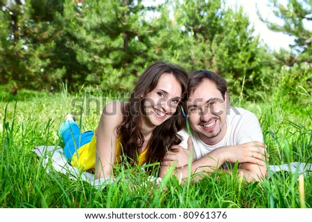 Young beautiful couple lying on blanket around green grass and trees. Looking and smiling at camera