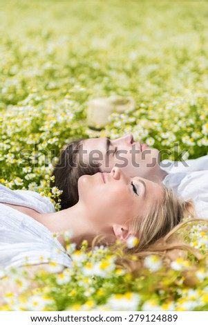 Young, beautiful couple lying on chamomile meadow, eyes closed - stock photo