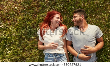 Young beautiful couple lying on the lawn and looking at each other smiling. Overhead view of happy young man and woman lying on the grass, with copy space. - stock photo