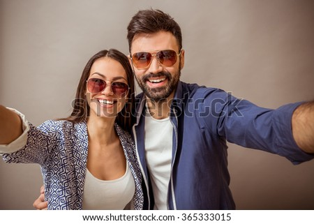 Young beautiful couple making self in glasses on a gray background - stock photo