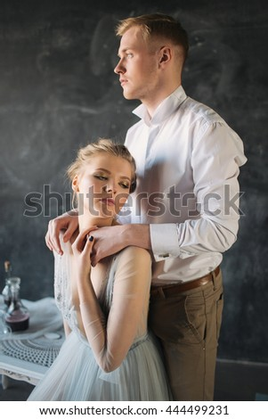Young beautiful couple of blonde newlyweds in love posing in decorated studio with flowers and candles