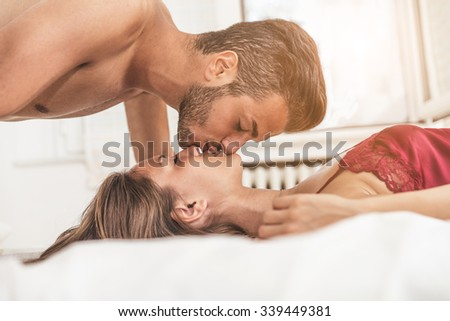 Young beautiful couple on a bed - Two lovers in the sleeping room, kissing on the bed  - stock photo