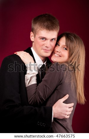 young, beautiful couple on a dark red background