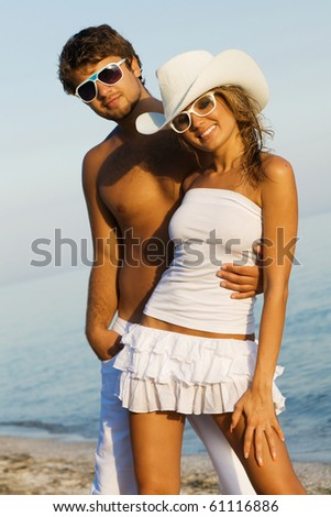 Young beautiful couple on a sea shore, focus on woman - stock photo