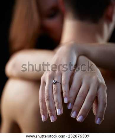 Young beautiful couple on black with female hands on foreground. Focus on ring - stock photo